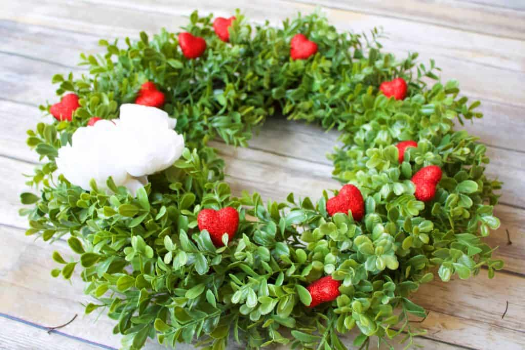 This easy to put together Valentine's Wreath is the perfect front door decor! Red hearts pop against a pretty green background. It's the perfect combo of spring and Valentines! #valentineswreath