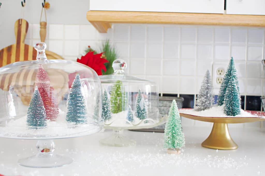 Christmas terrarium made with only two materials: snow flakes and bottle Christmas trees. Simple, beautiful, and budget friendly! #christmasterrarium #bottlebrushtrees