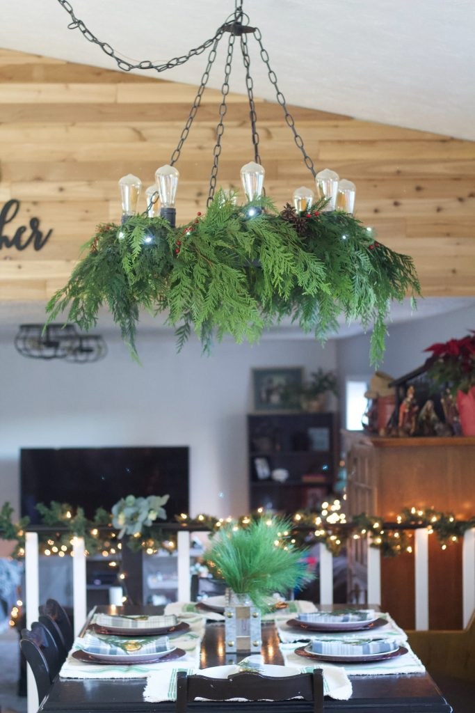 Decorating a chandelier with greenery for Christmas is a great way to add next level cozy to your dinning room or living area. Plus its easy! #garland #chandelierdecor