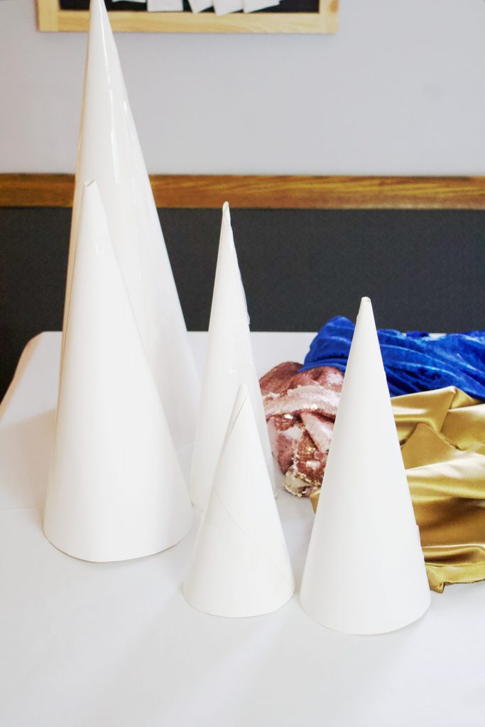 These stunning paper Christmas Tree Cones are so easy to make. All you need is poster board, glue, scissors, tape, and fabric! Use your imagination to come up with all different kinds of trees.