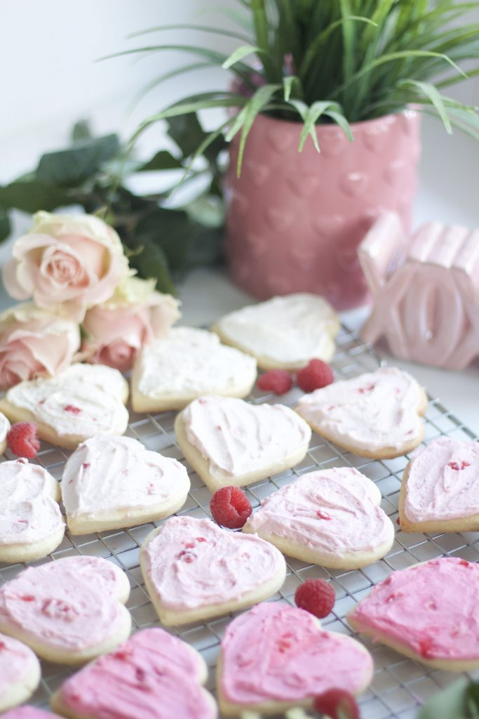 Looking for an amazing sugar cookie with a twist? A surprise orange raspberry buttercream frosting! Watch your guests light up when they bite into these gorgeous, delicious, ombre sugar cookies. #valentinescookies #sugarcookies